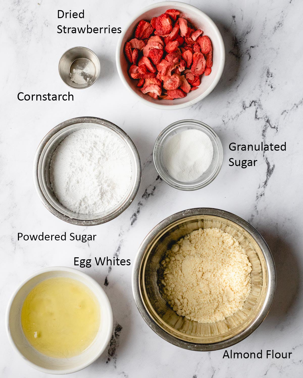 Strawberry Macaron ingredients: freeze-dried strawberries, egg whites, almond flour, granulated sugar, confectioners' sugar, and cornstarch.