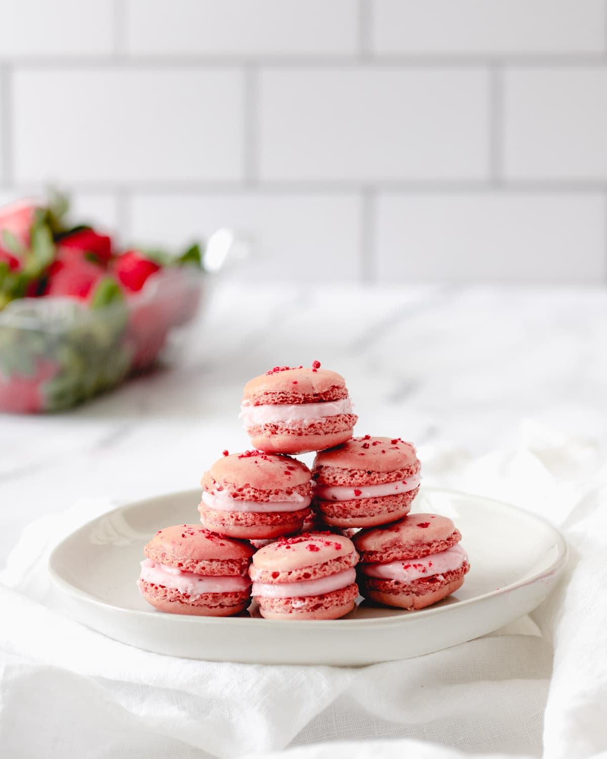 Strawberry macarons stacked on a round plate, with a carton of strawberries in the background.
