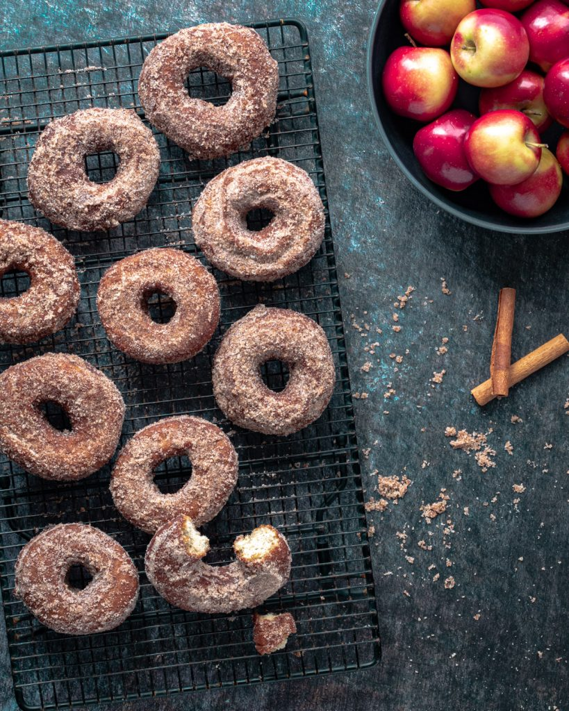 Apple cider donuts on a cooling rack next to a basket of apples.