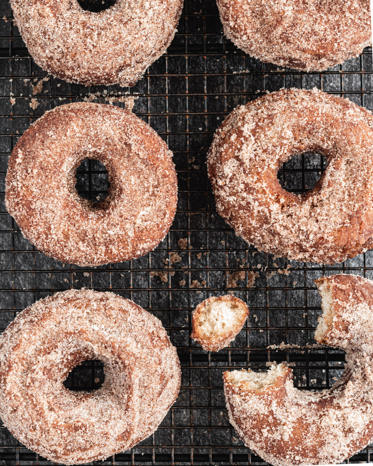 Apple cider donuts dusted in powdered sugar and laying on a cutting board. One donut has a bite out of it.