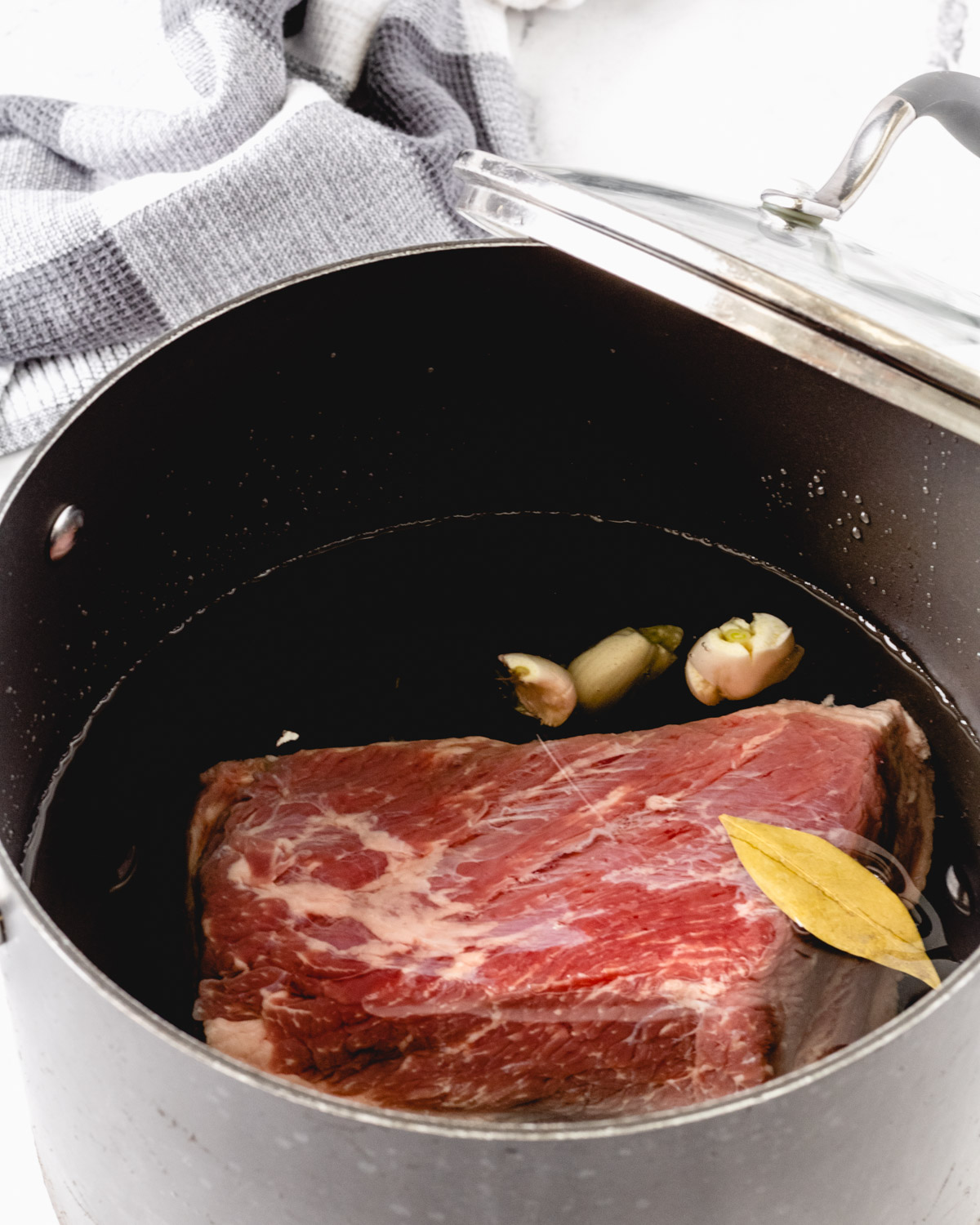 Corned beef in a big pot with water and seasonings.