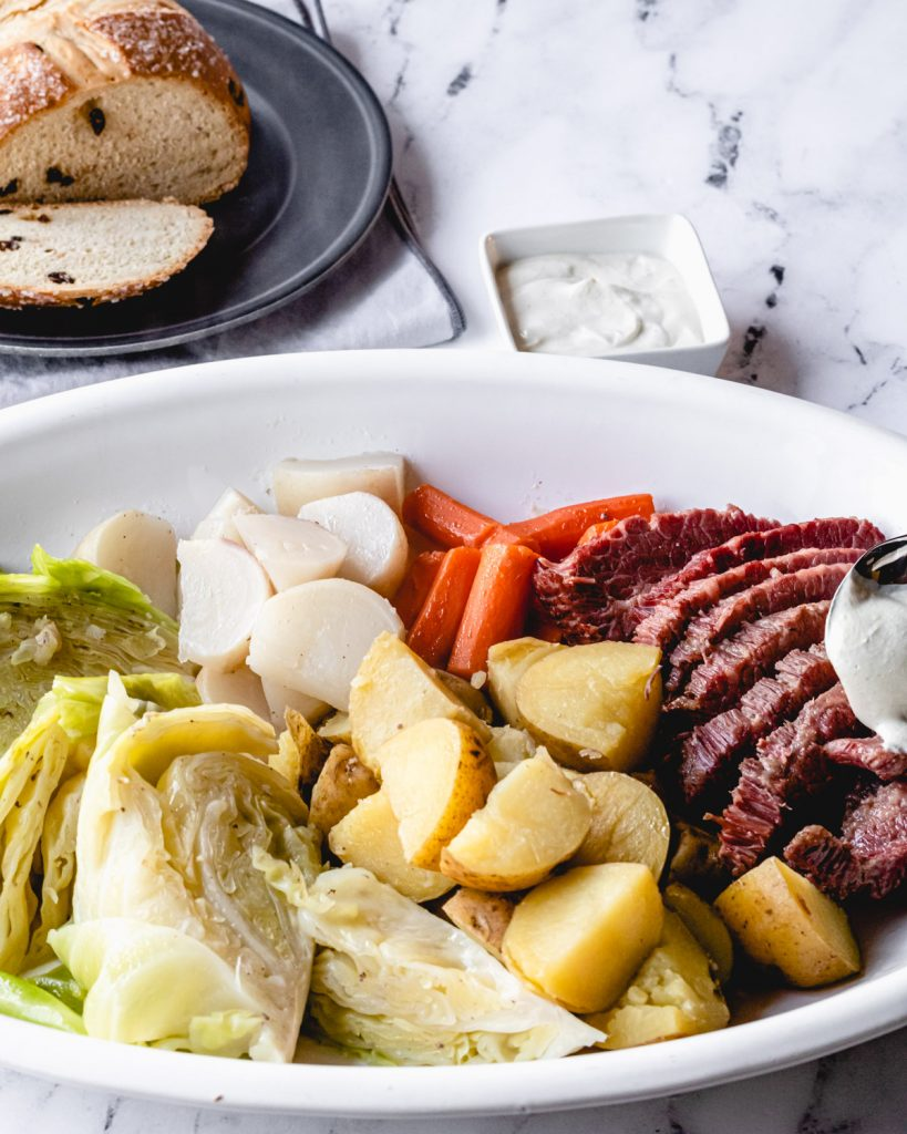 Platter of corned beef with vegetables, and behind it is a ramekin of mustard cream sauce and Irish soda bread on a plate.