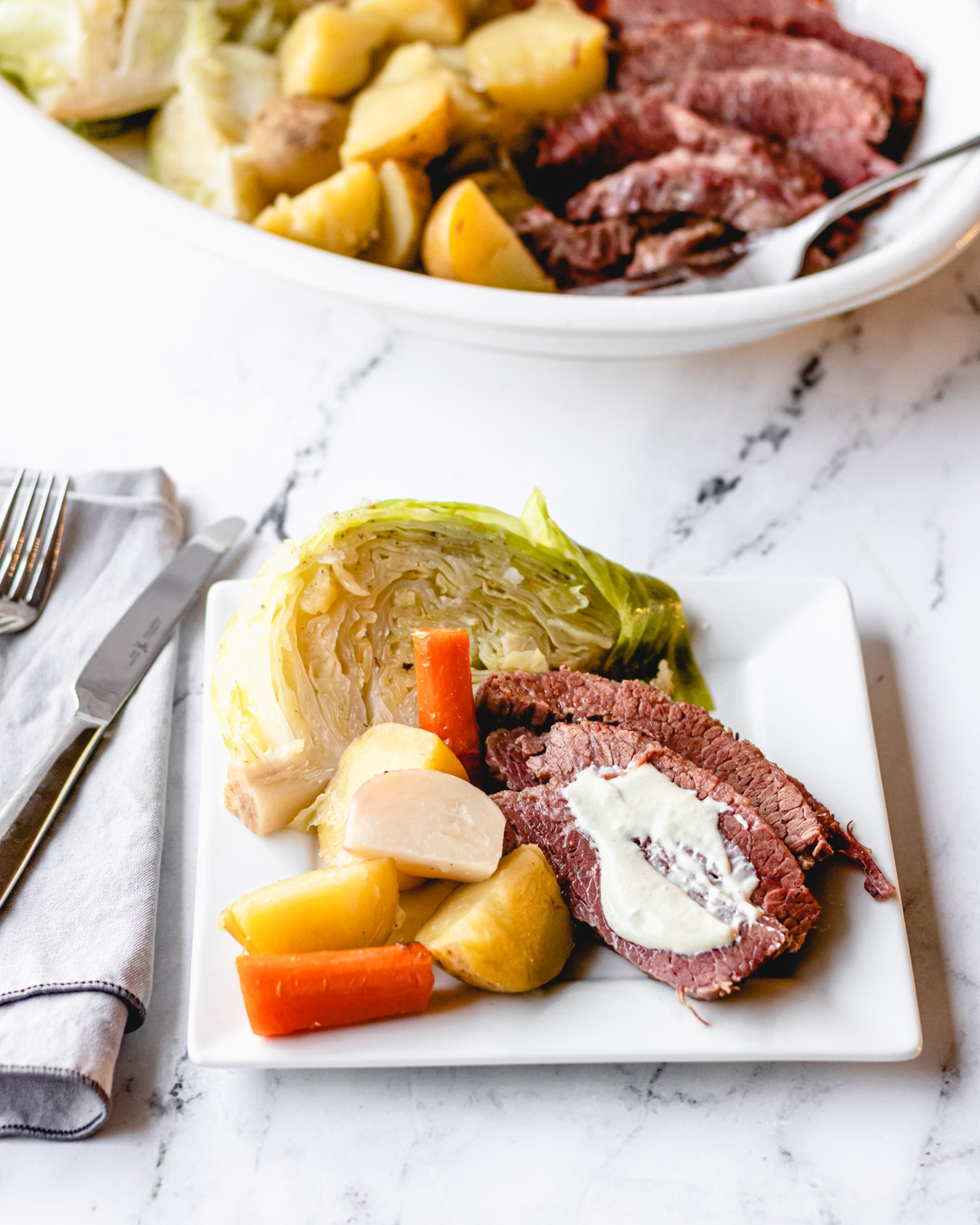Plate of corned beef topped with mustard cream sauce, with boiled cabbage, potatoes,turnips, and carrots.