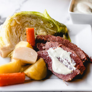 Corned beef on a plate with boiled vegetables and mustard sauce smeared across the beef.