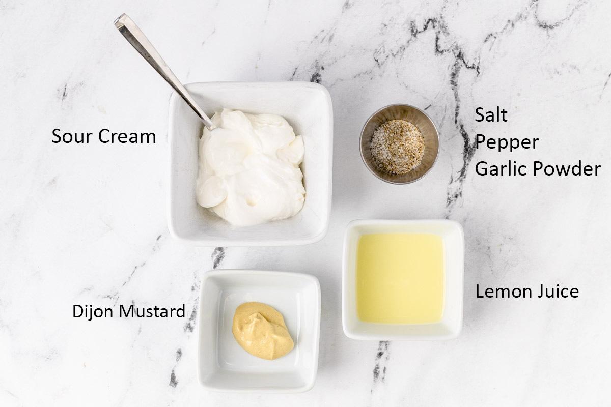 Creamy mustard sauce ingredients: sour cream, dijon mustard, salt, pepper, garlic powder, and lemon juice.