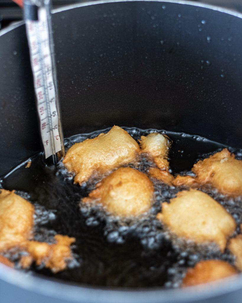 Funnel cake bites frying in oil.