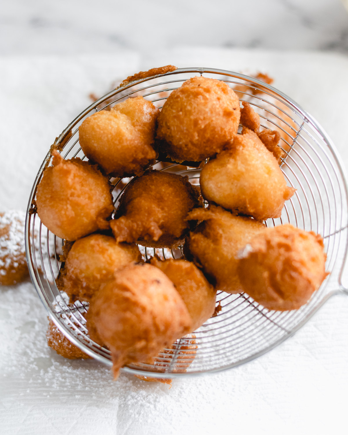 Cooked bites in a stainless slotted scoop, ready to cool on paper towel.