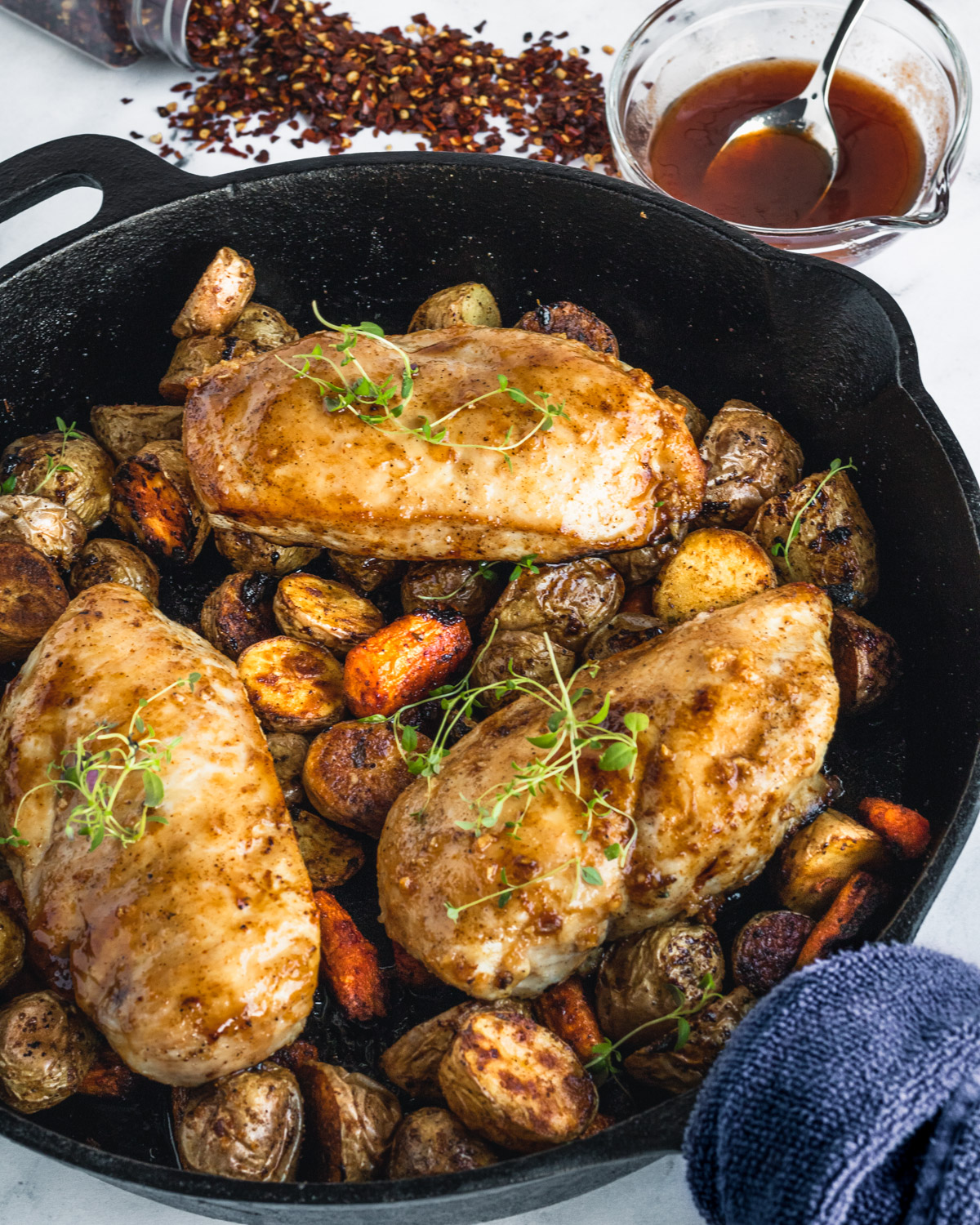 Cast iron skillet with roasted potatoes, carrots, and hot honey chicken - a bowl of hot honey and crushed red peppers at top of photo.