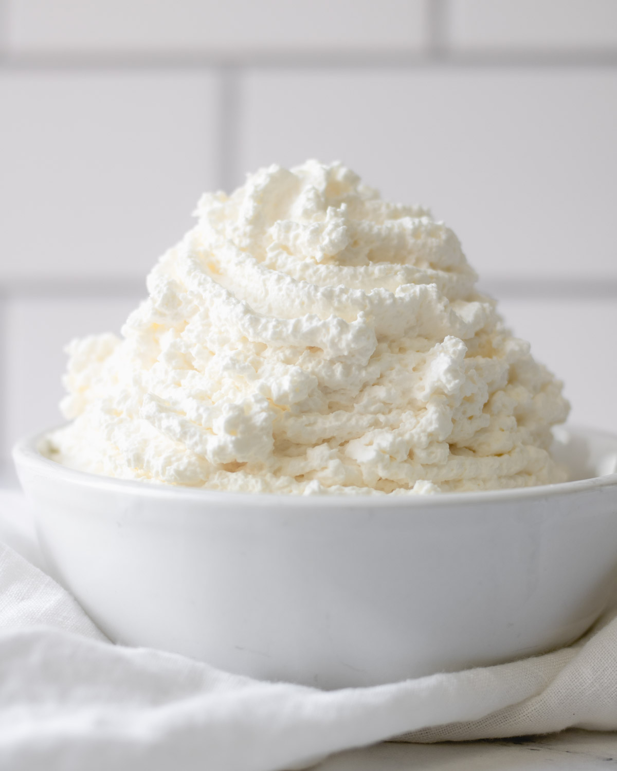 whipped cream piled into a bowl piled high.