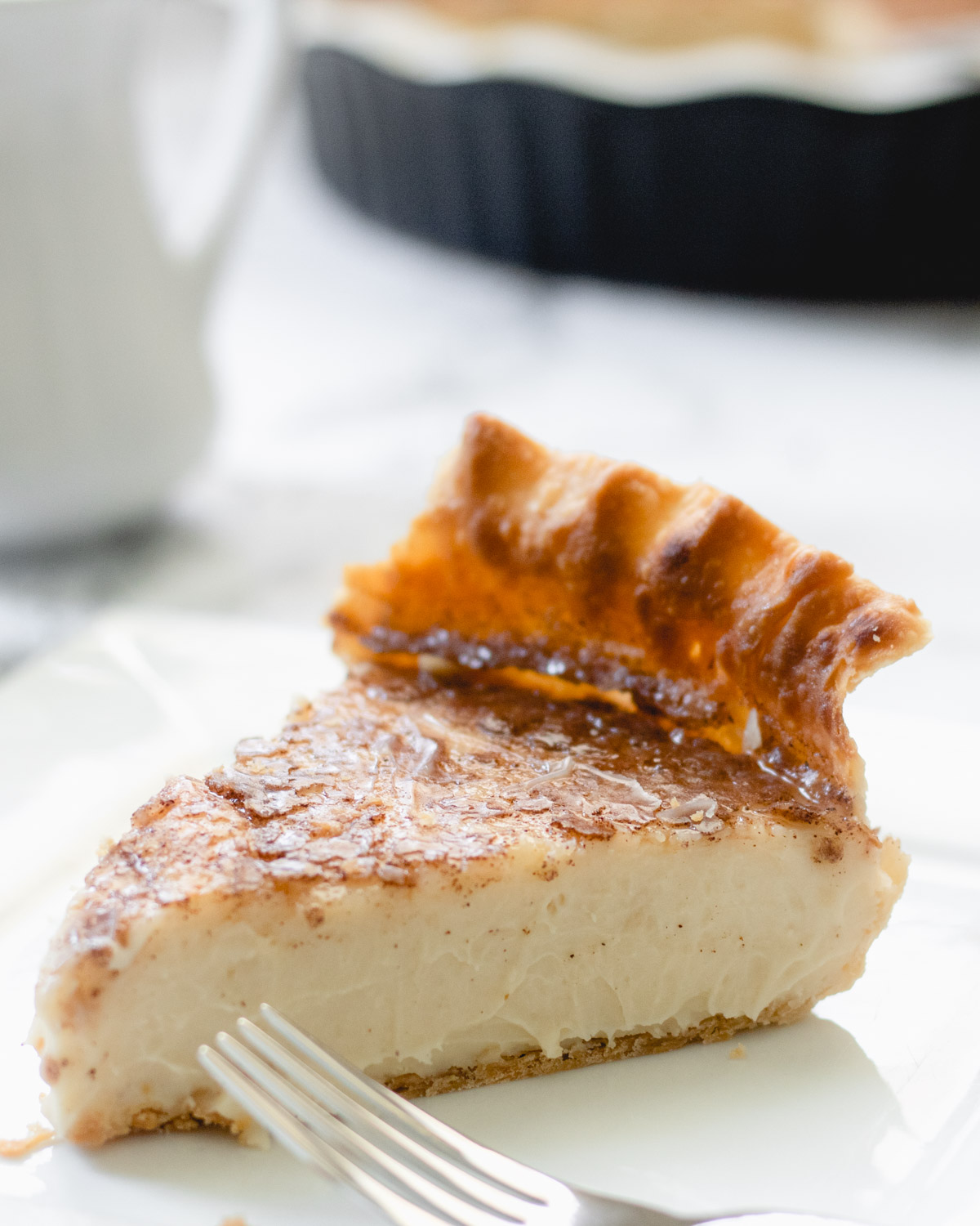 Slice of sugar cream pie topped with caramelized cinnamon sugar, on a plate with a fork.