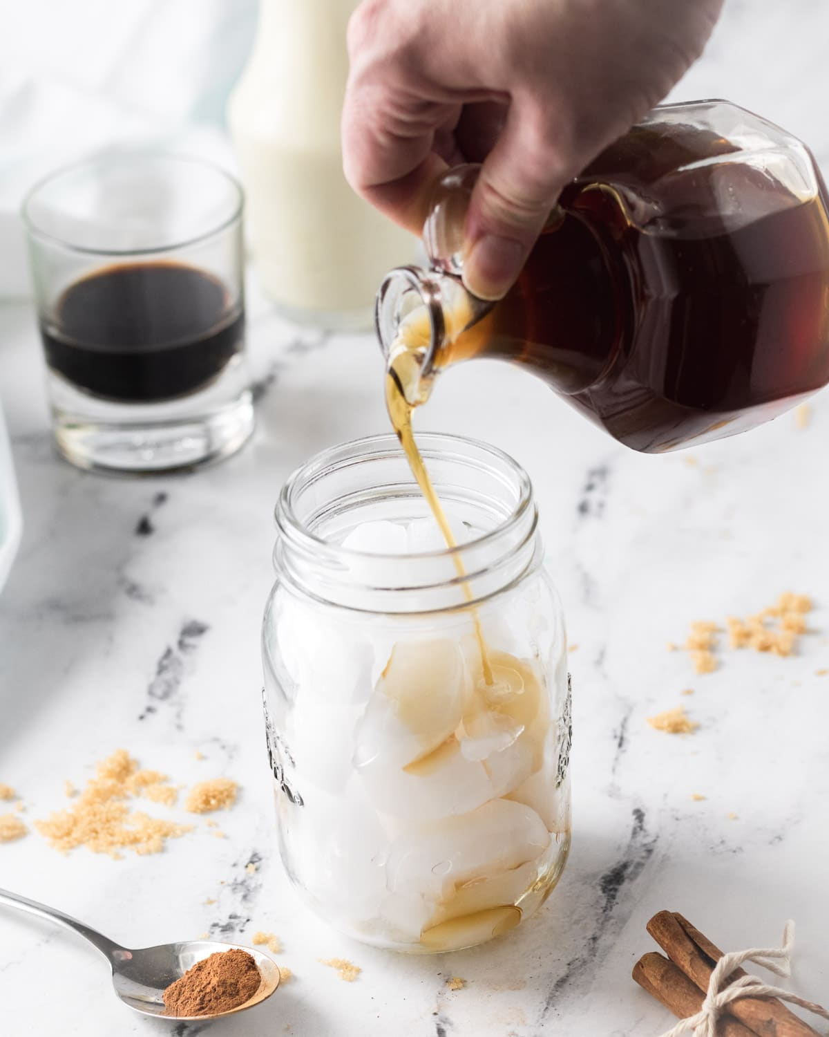 Pouring brown sugar simple syrup into mason jar filled with ice.
