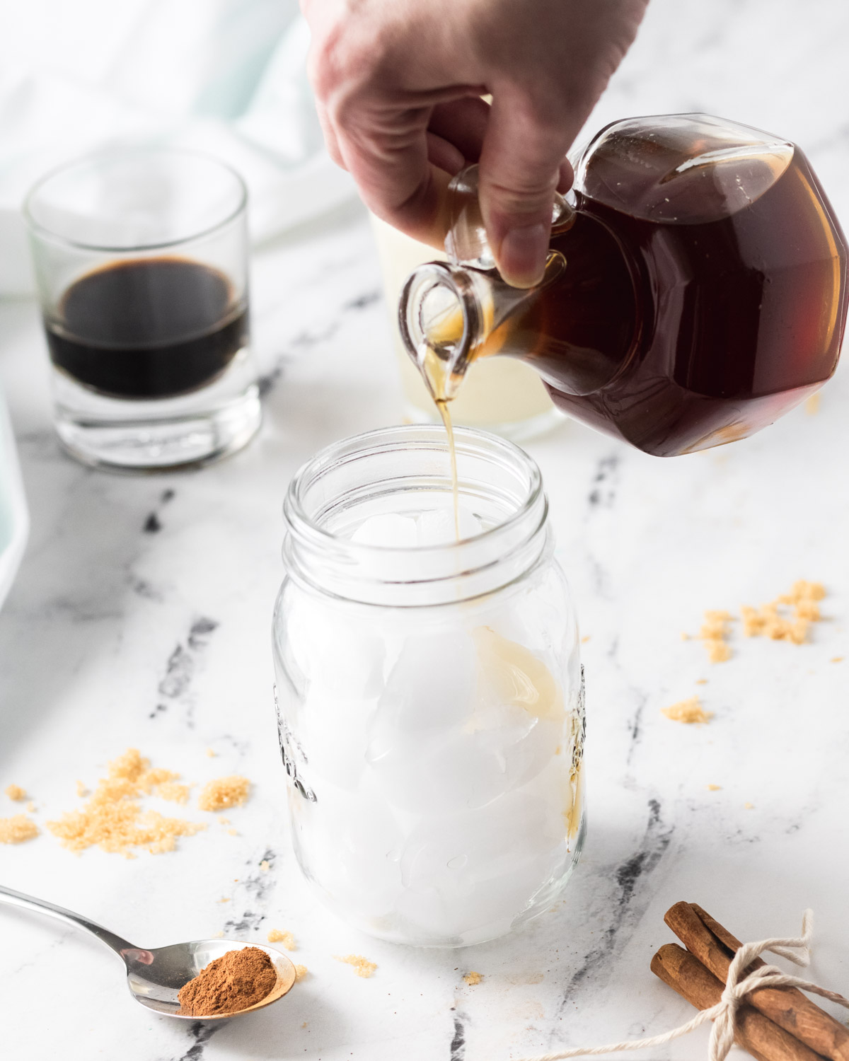 Pouring simple syrup into a mason jar filled with ice.