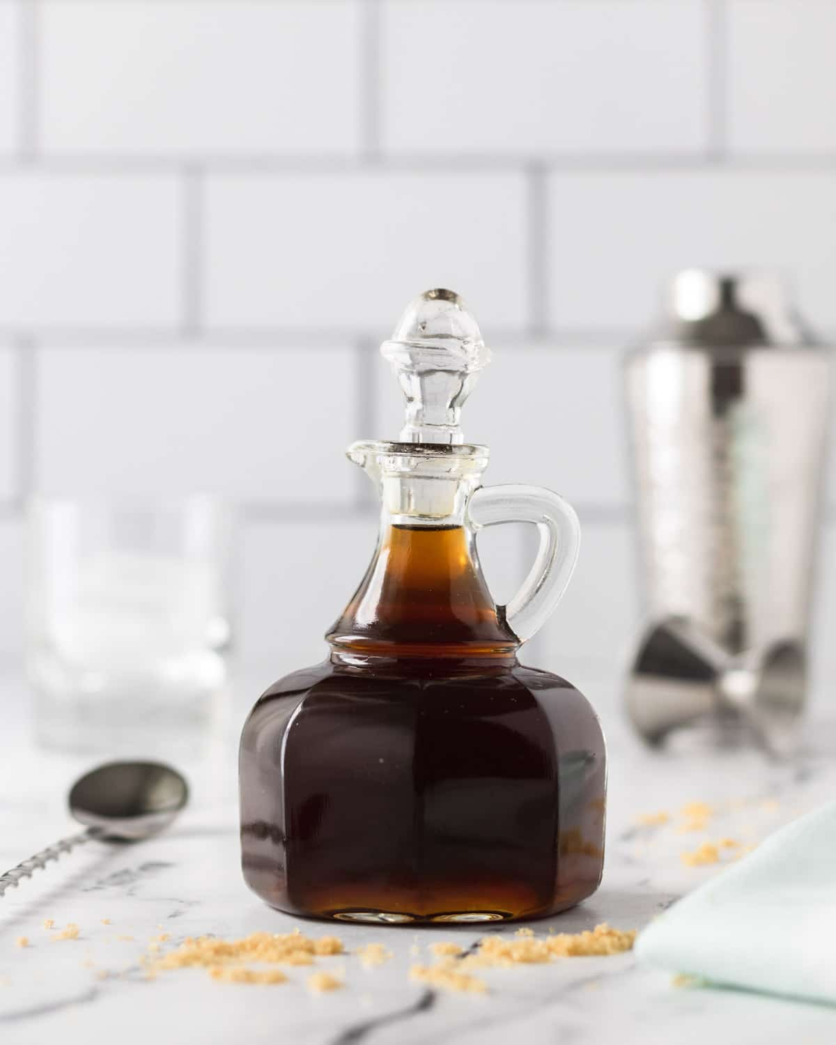 Glass pitcher of brown sugar simple syrup, with cocktail spoon, shaker, and jigger.