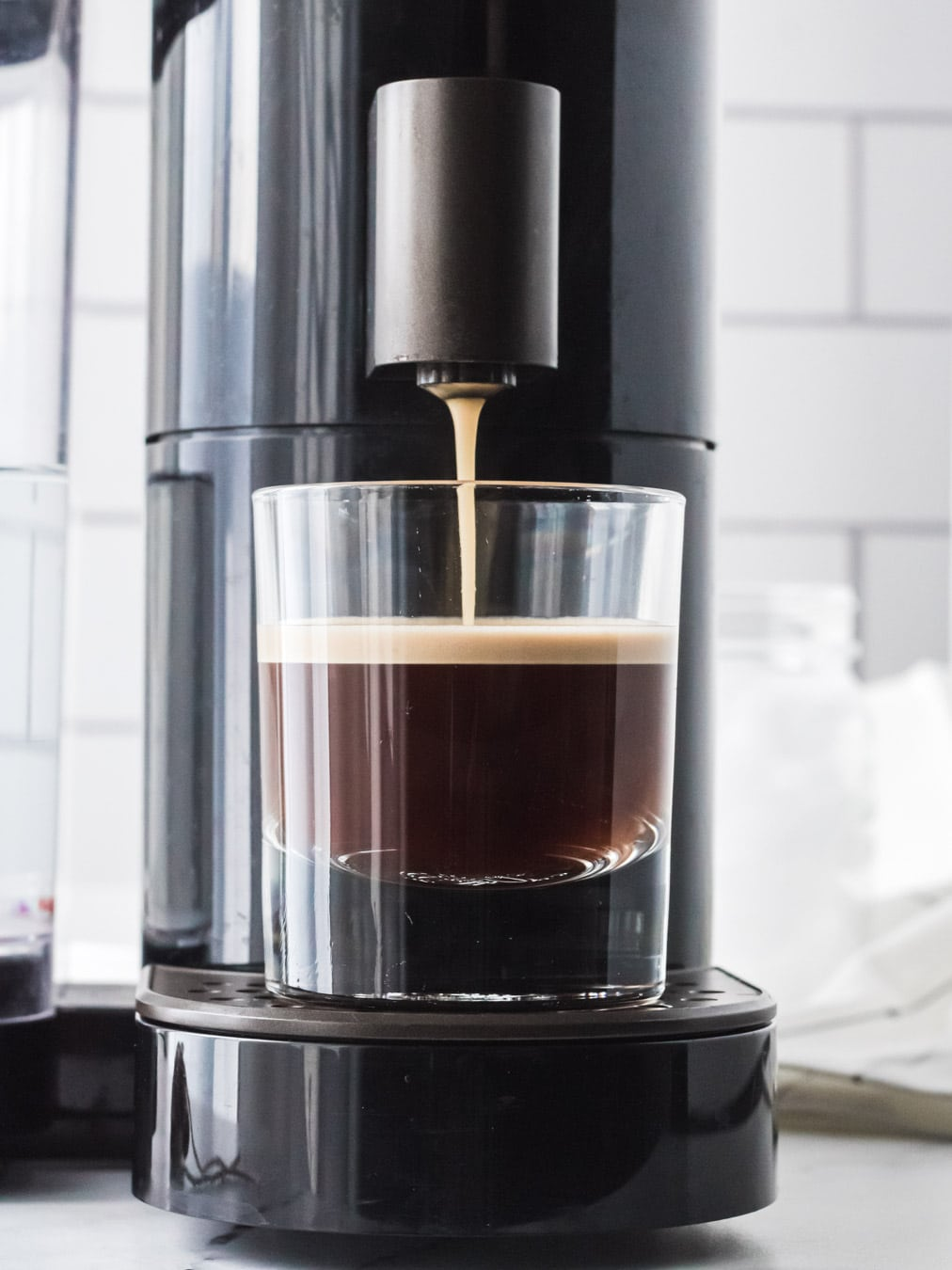A machine is pulling shots of espresso into a clear glass.