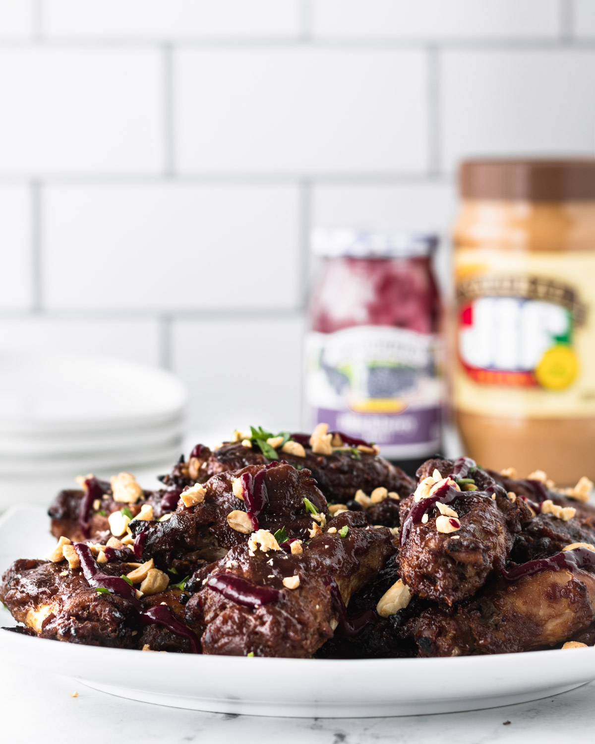 Plate of peanut butter and jelly chicken wings, with a jar of peanut butter and a jar or jelly in the background.