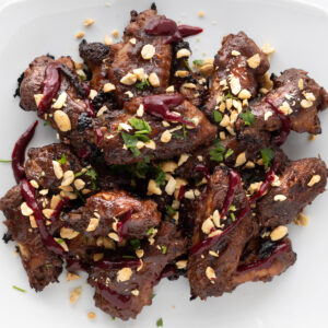 Plate of peanut butter and jelly wings topped with chopped peanuts, cilantro, and blackberry coulis.