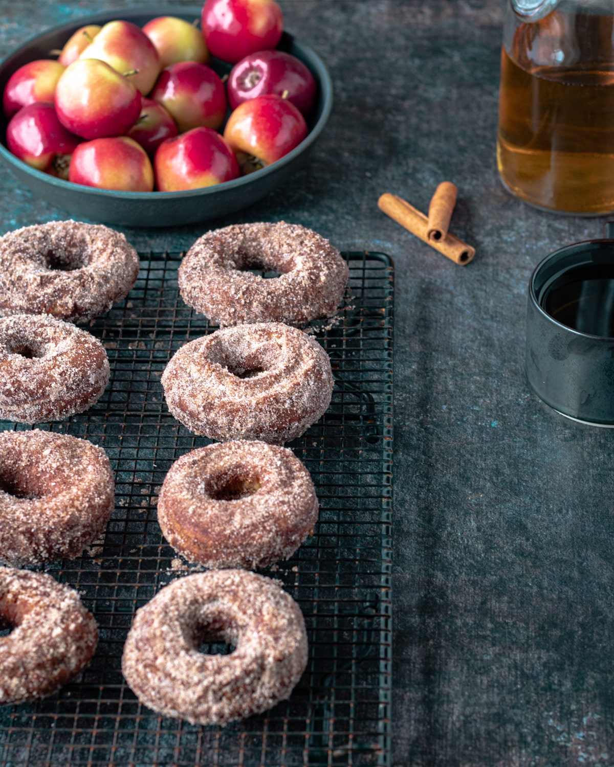 Two rows of apple cider donuts, with a bowl of apples, cinnamon sticks, and cider.