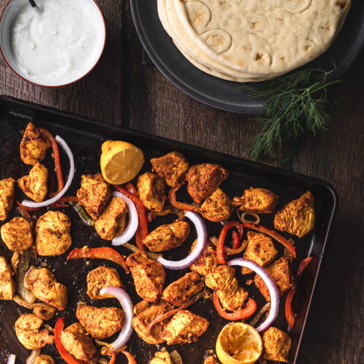 Sheetpan of chicken schwarma with a plate of pitas and a bowl of dill yogurt sauce.