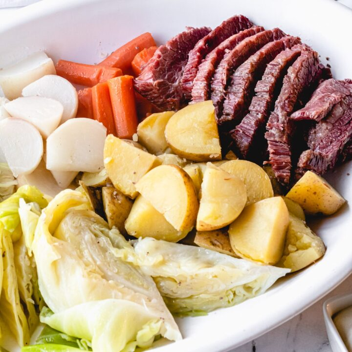 Corned beef on a platter with boiled cabbage, carrots, potatoes, and turnips.