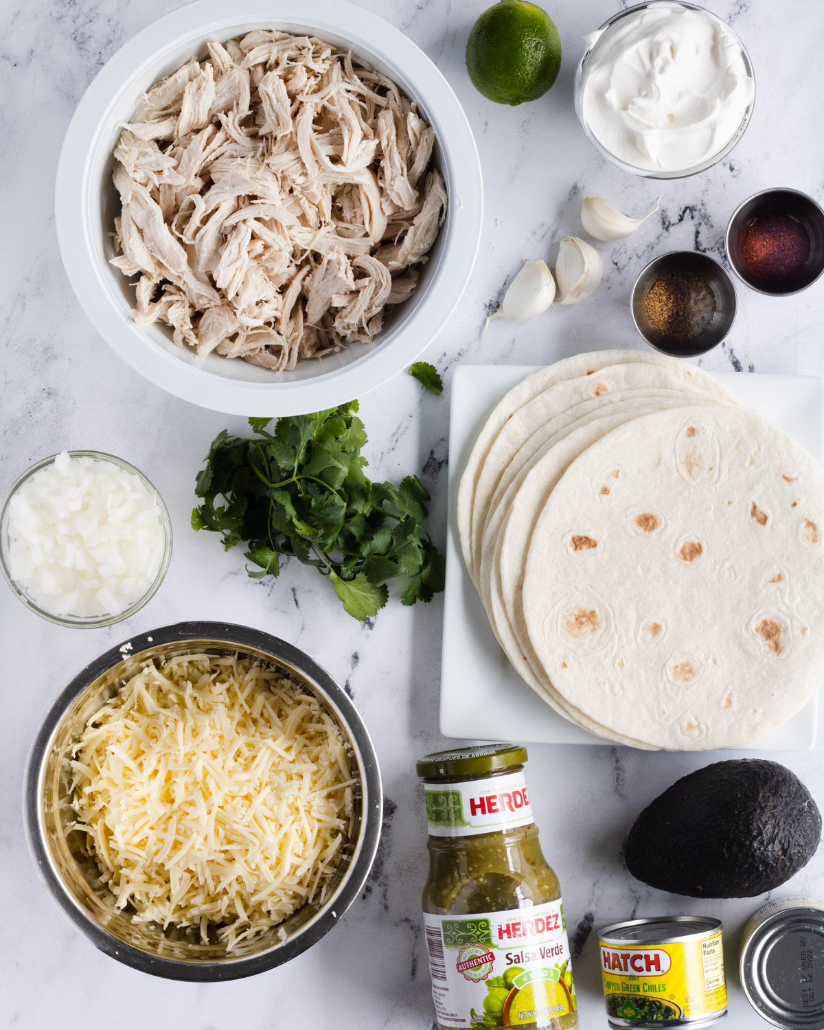 Ingredients for enchiladas: chicken, lime, sour cream, garlic, chile powder, cumin, tortillas, avocado, green chiles, salsa verde, shredded cheese, cilantro, and chopped onion.
