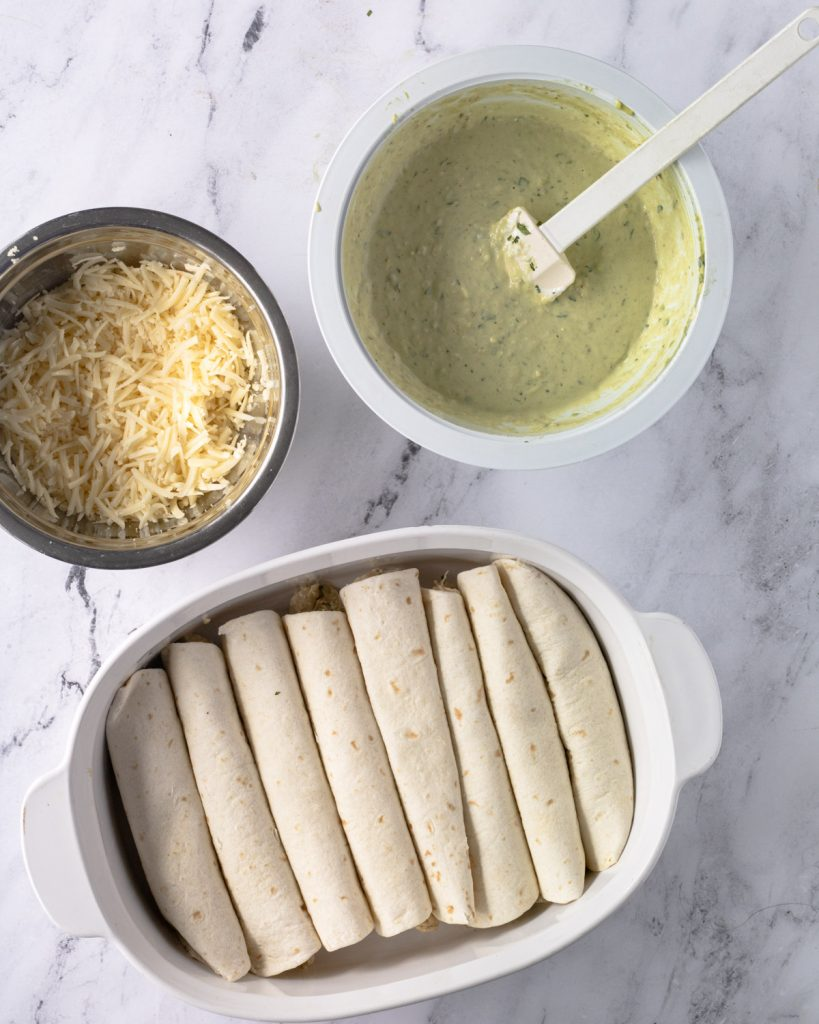 The components of the enchiladas: A pan of filled and rolled tortillas, creamy salsa verde sauce, and shredded cheese.