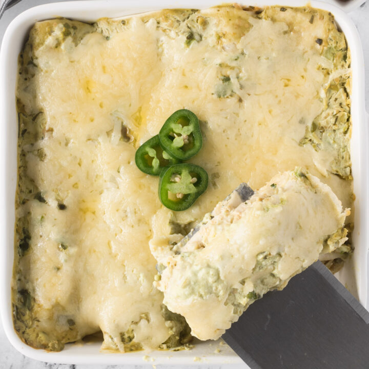 Close up of green chile chicken enchilada casserole, with one enchilada being removed from pan.