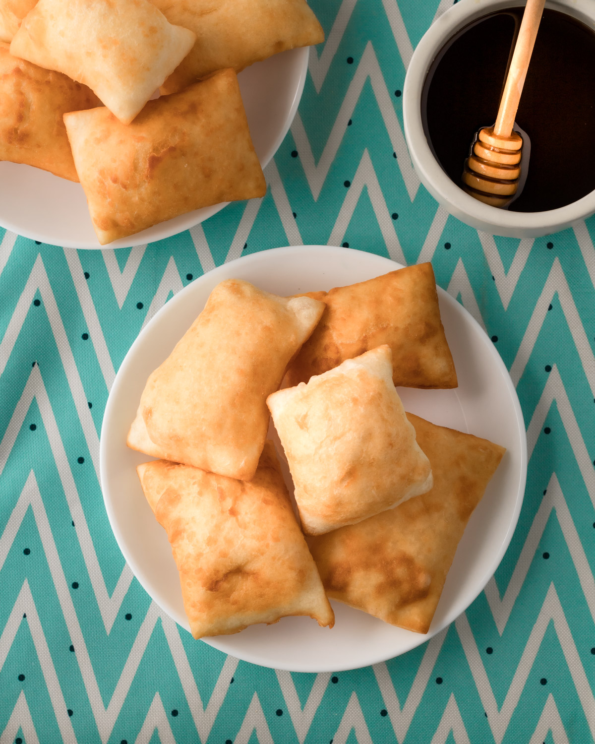 Plate of sopapillas on a teal zig zag cloth, with bowl of honey.