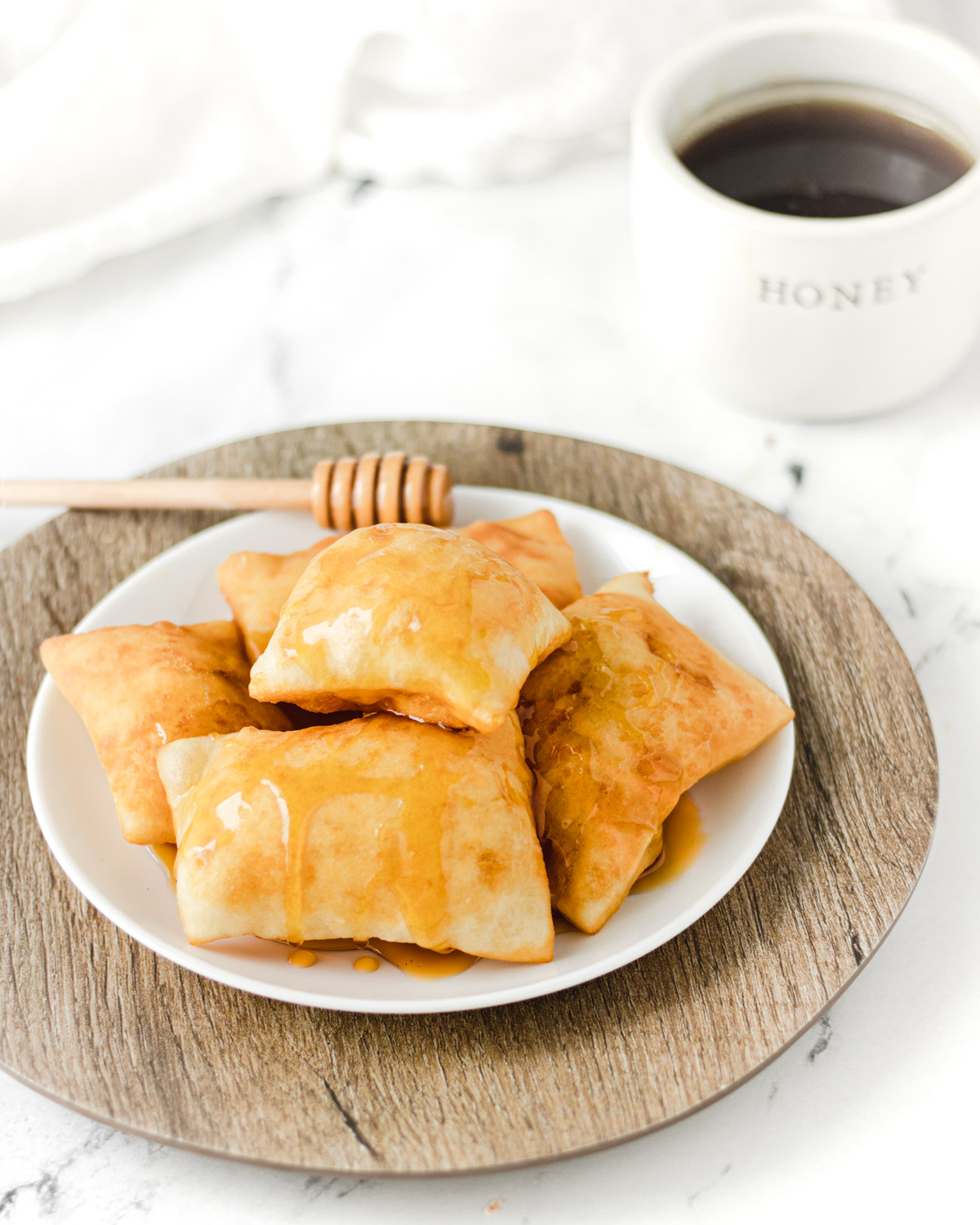 plate of sopapillas with a honey stick resting on plate and bowl of honey in background.
