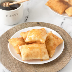 Sopapillas on a plate, with a brown plate underneath and bowl of honey on the side.