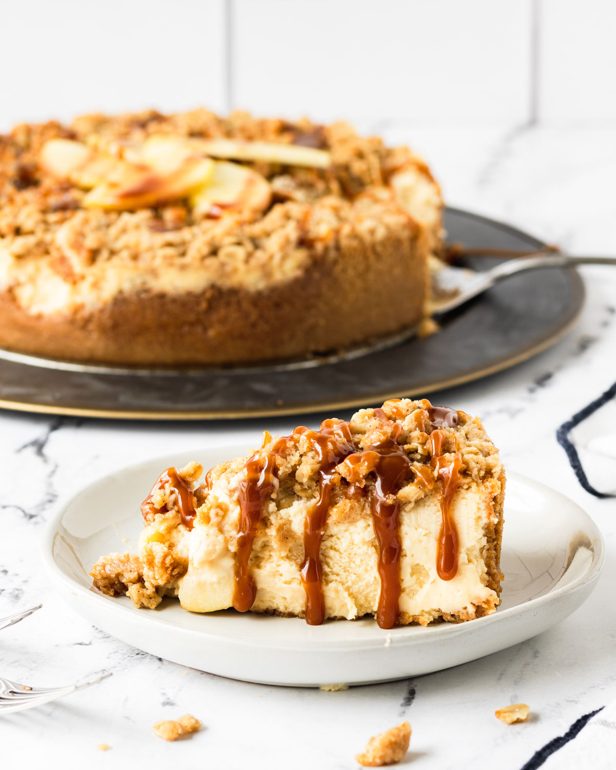 Slice of caramel apple crumble cheesecake, with caramel dropping down the sides, and the whole cheesecake in the background.