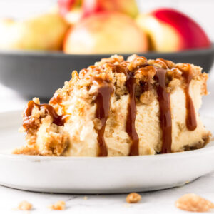 Slice of caramel apple crumble cheesecake with a bowl of apples in the background.