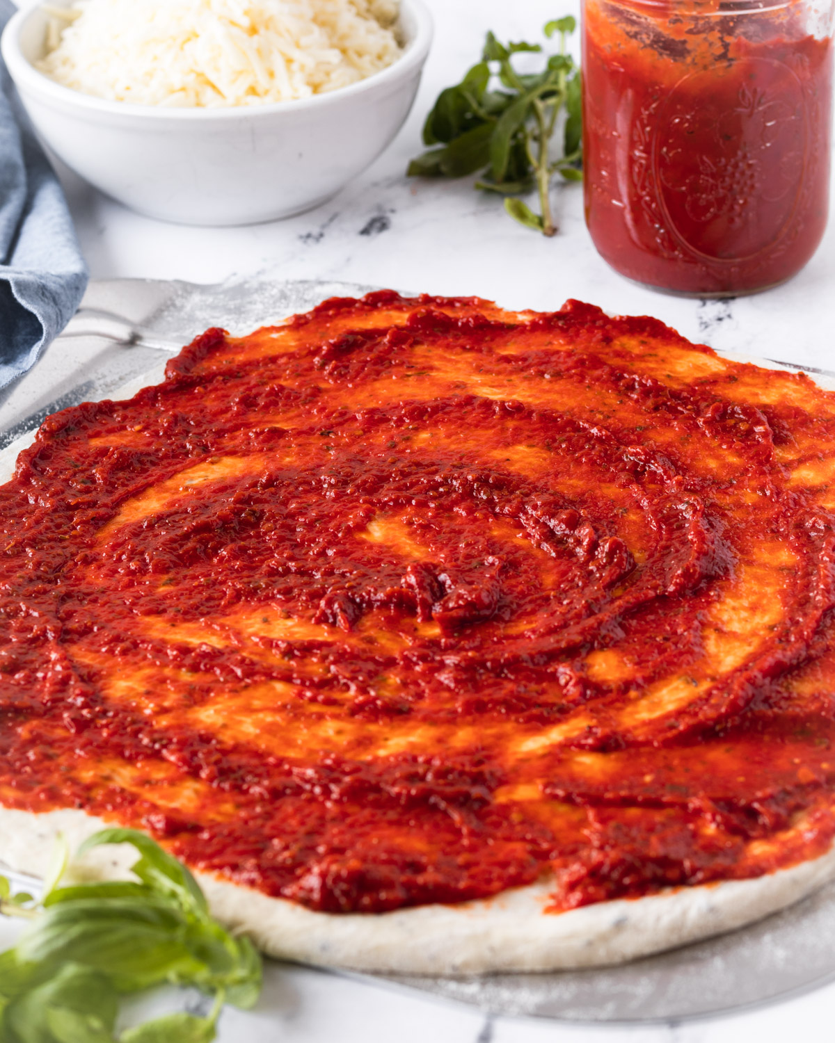 Pizza sauce spread thick on pizza dough, with a jar of sauce and a bowl of shredded cheese in the background.
