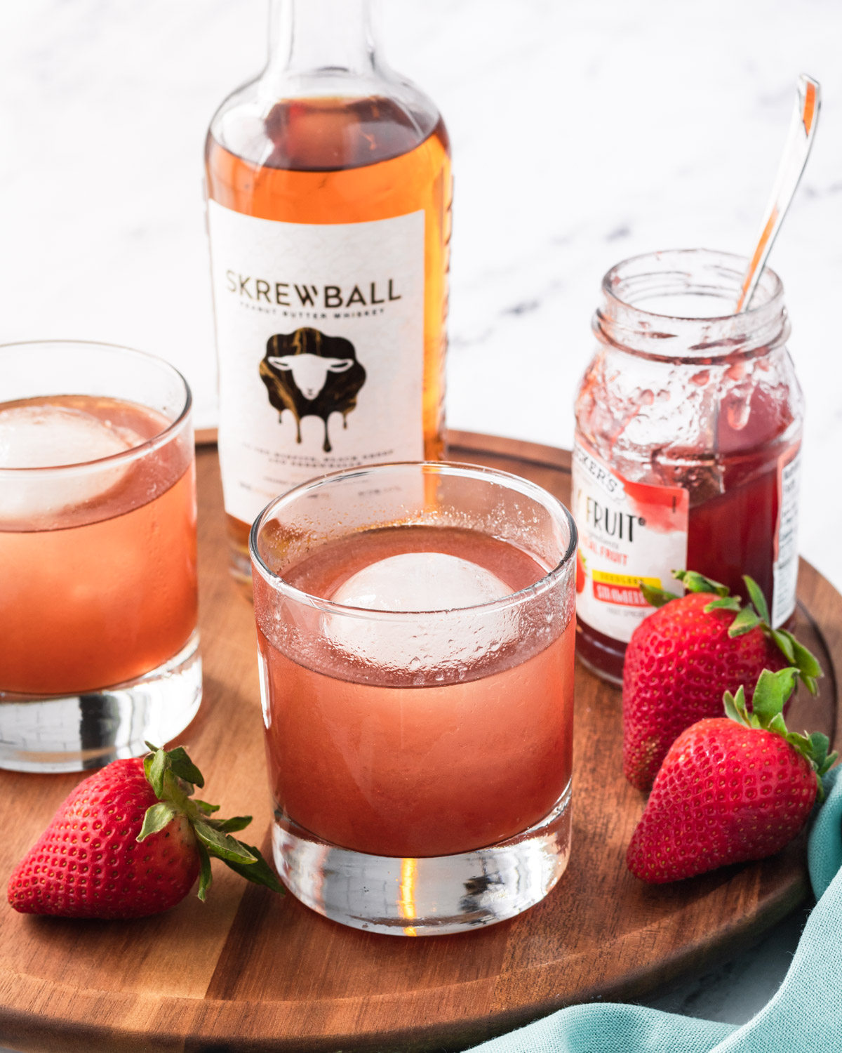 Two PB&J cocktails in rocks glasses, on  a wooden tray with Skrewball whiskey, jelly, and some strawberries.