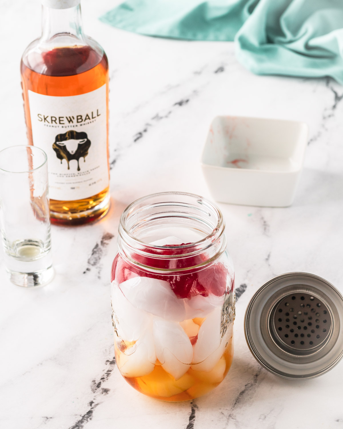 Strawberry jelly and peanut butter whiskey have been poured over the ice in the mason jar shaker.
