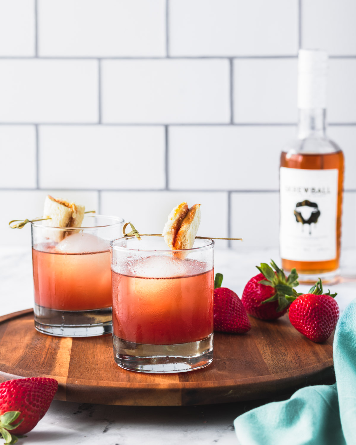 Two PB&J cocktails on a wooden serving tray with Skrewball whiskey in background.