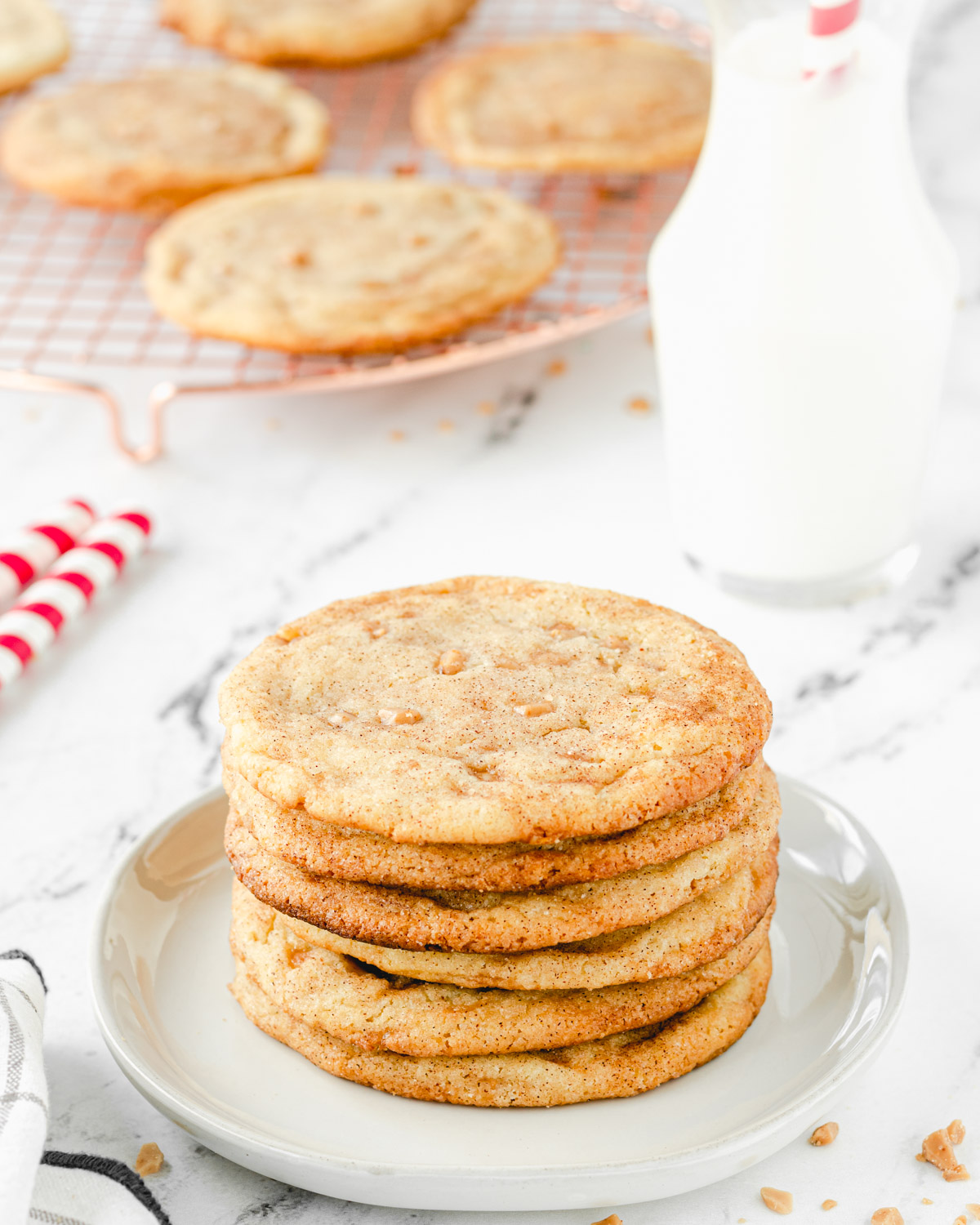Stack of brown butter toffeedoodle cookies with a carafe of milk and a cooling rack of cookies.