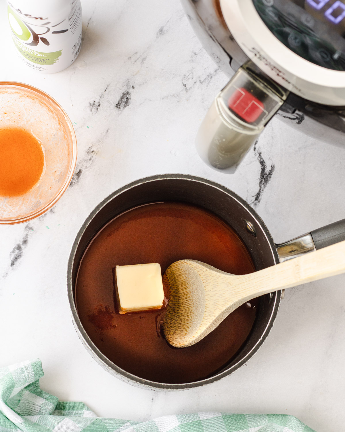 Wing sauce in a saucepan with a wooden spoon.
