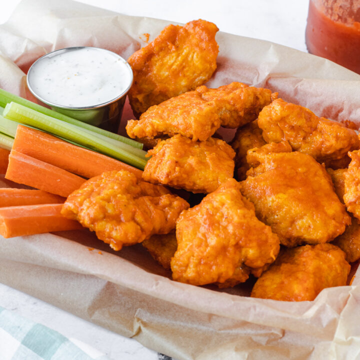 Basket of air fryer boneless chicken wings with ranch dip, carrots, and celery.