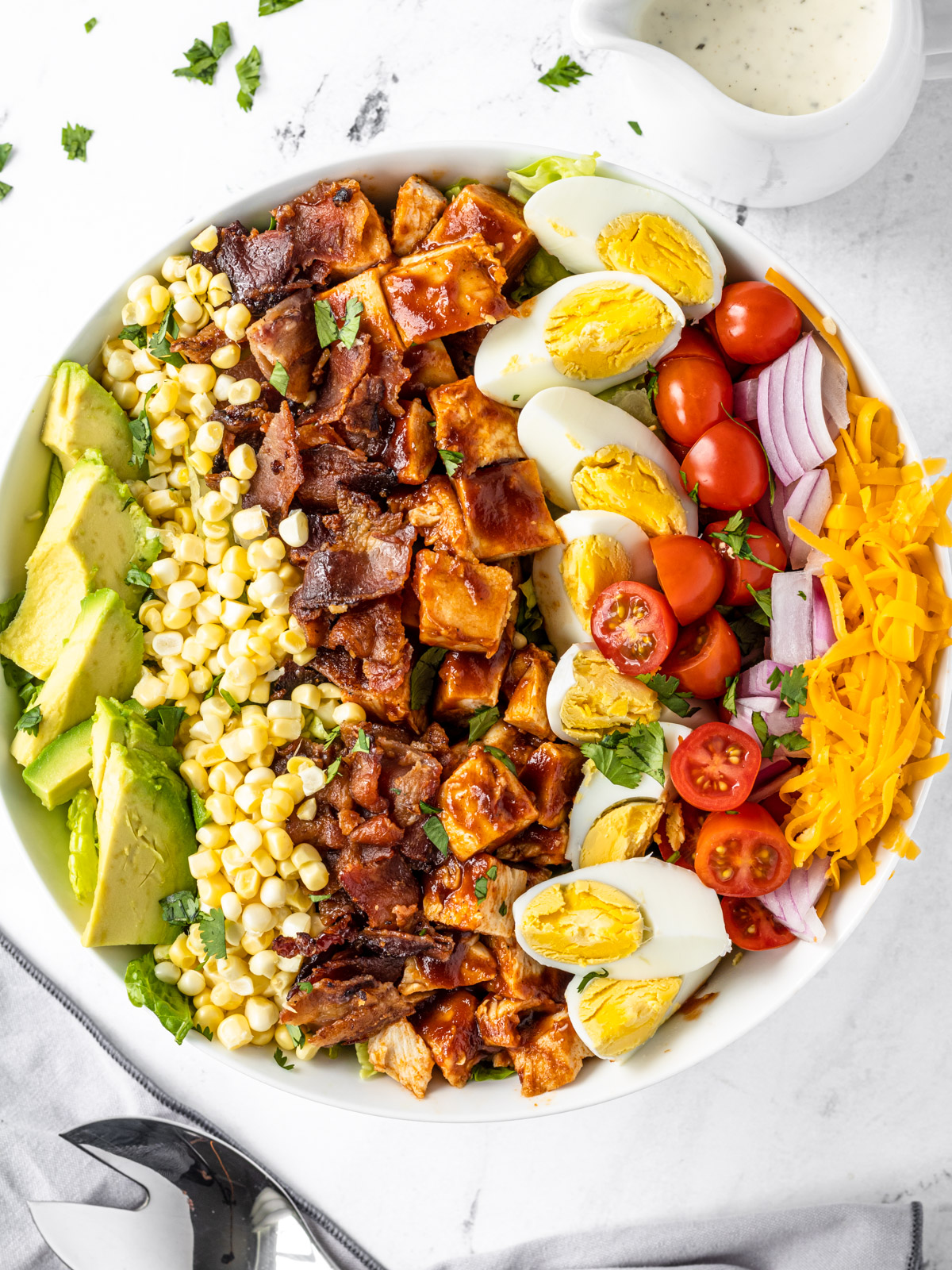 Bowl of bbq chicken cobb salad with a small pitcher of ranch dressing.