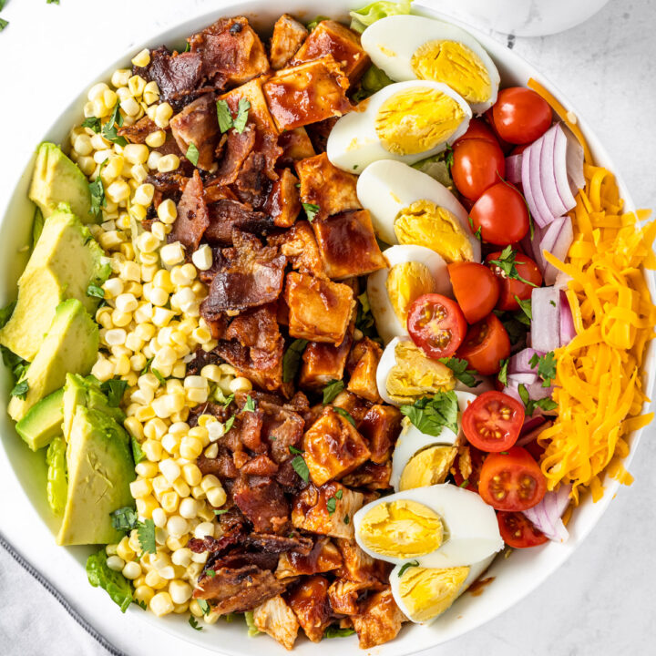 Close up of bowl of bbq chicken cobb salad with a small pitcher of ranch dressing.