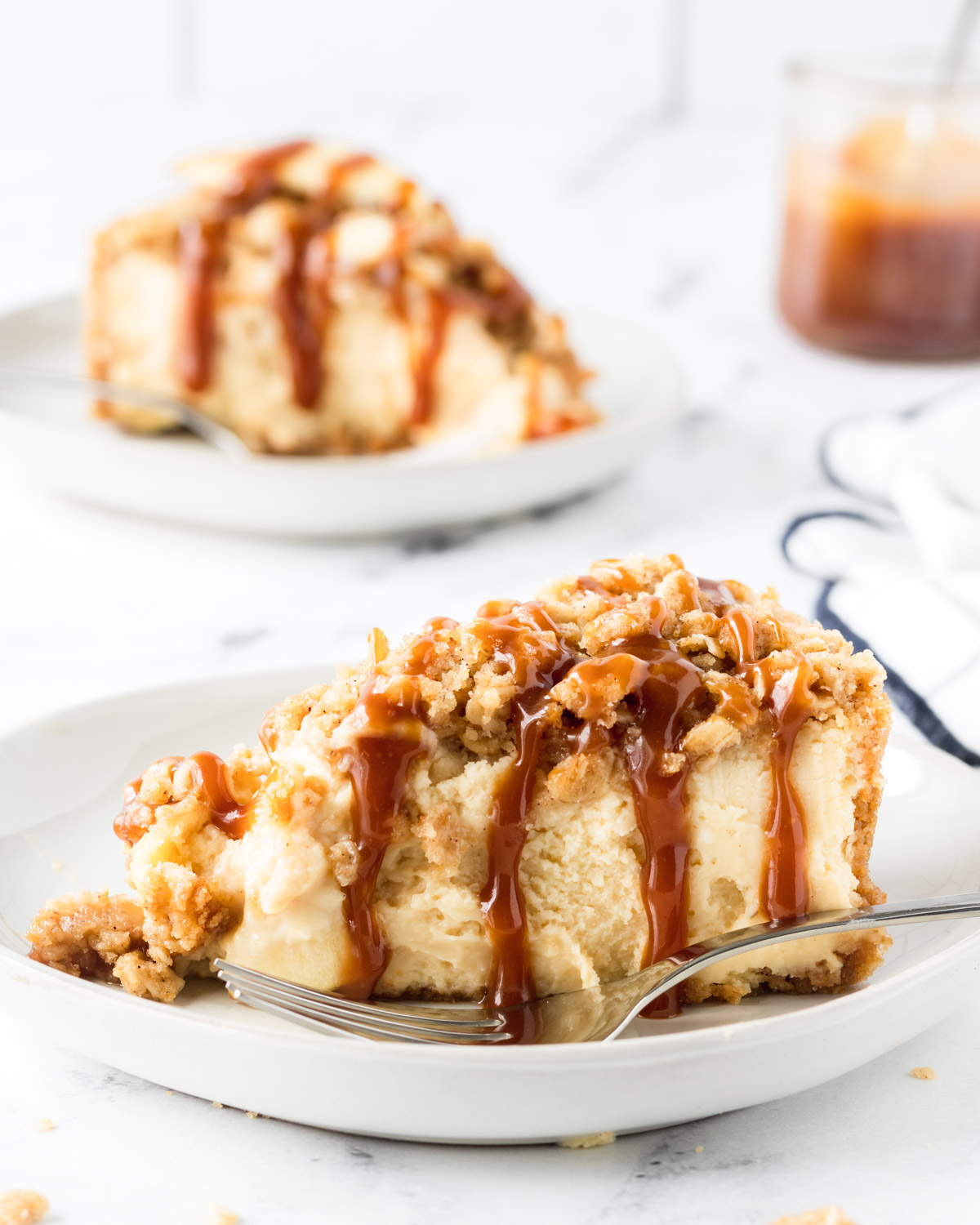 Two slices of cheesecake with caramel dropping down.