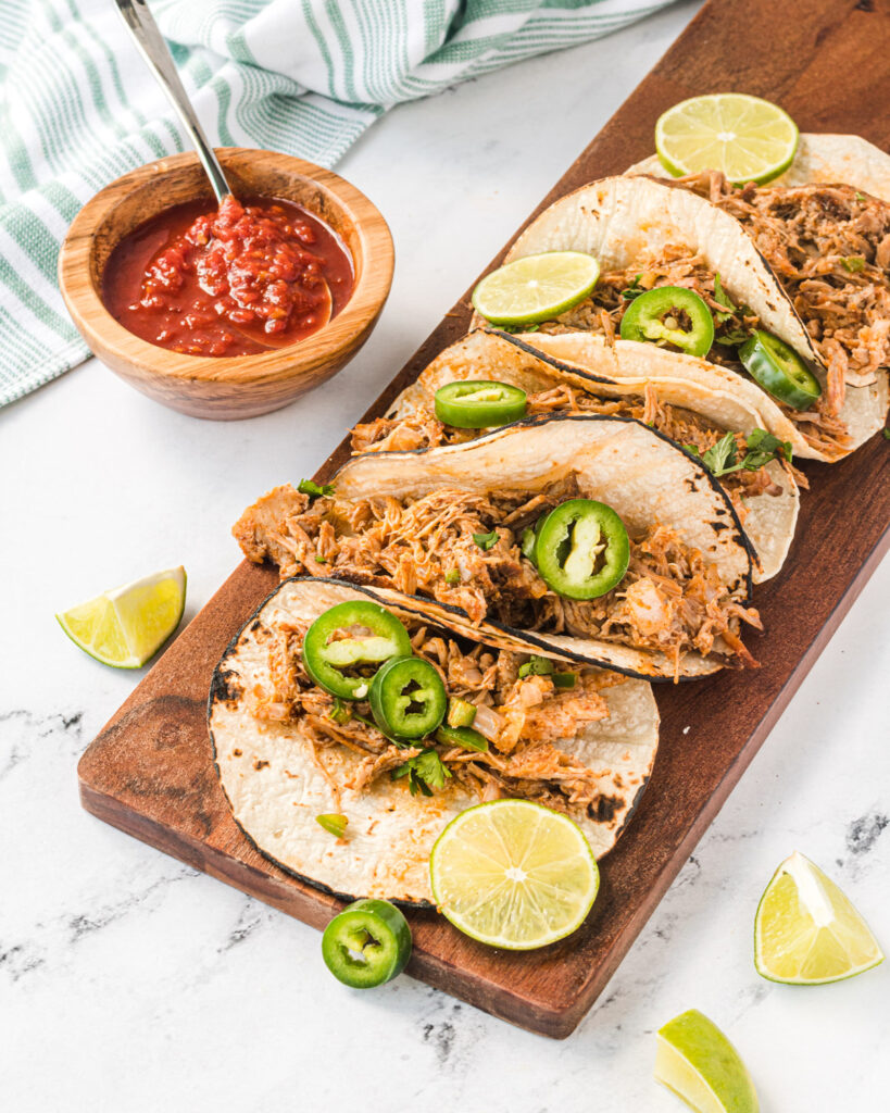 5 carnitas tacos on a wooden platter, garnished with jalapenos and limes.