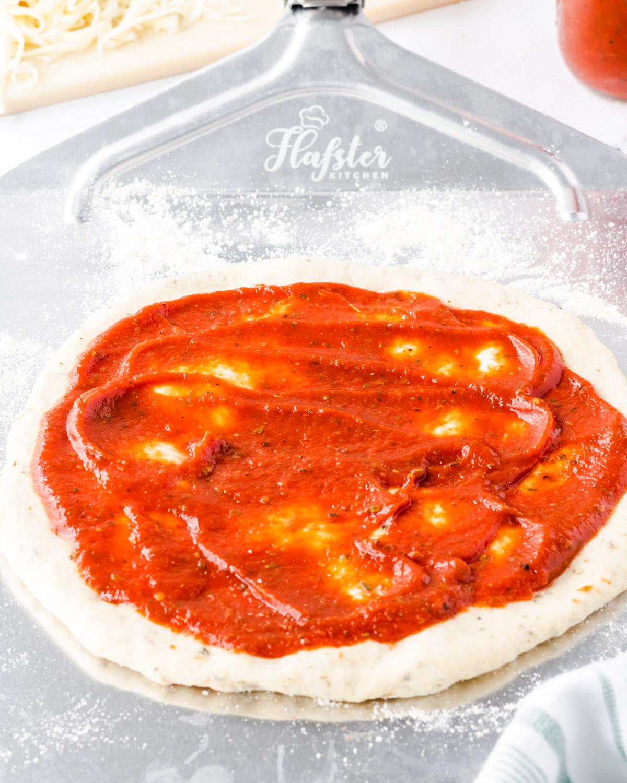 Pizza sauce spread across pizza dough.