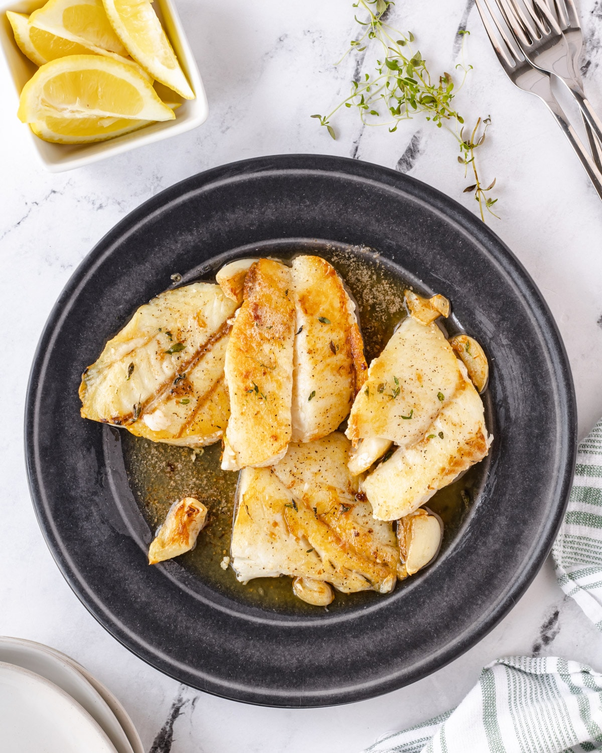 garlic butter-basted fish on a grey plate with sliced lemonds and a few sprigs of thyme above the plate.