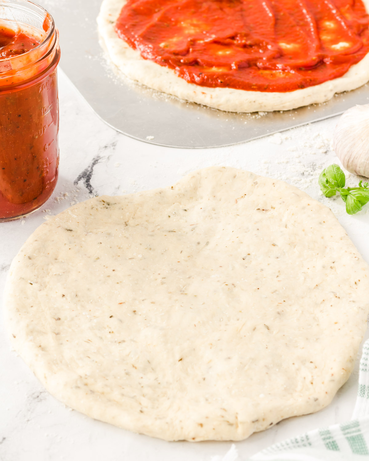 Stretched out dough, ready to top, with the sauce in a mason jar on the side.