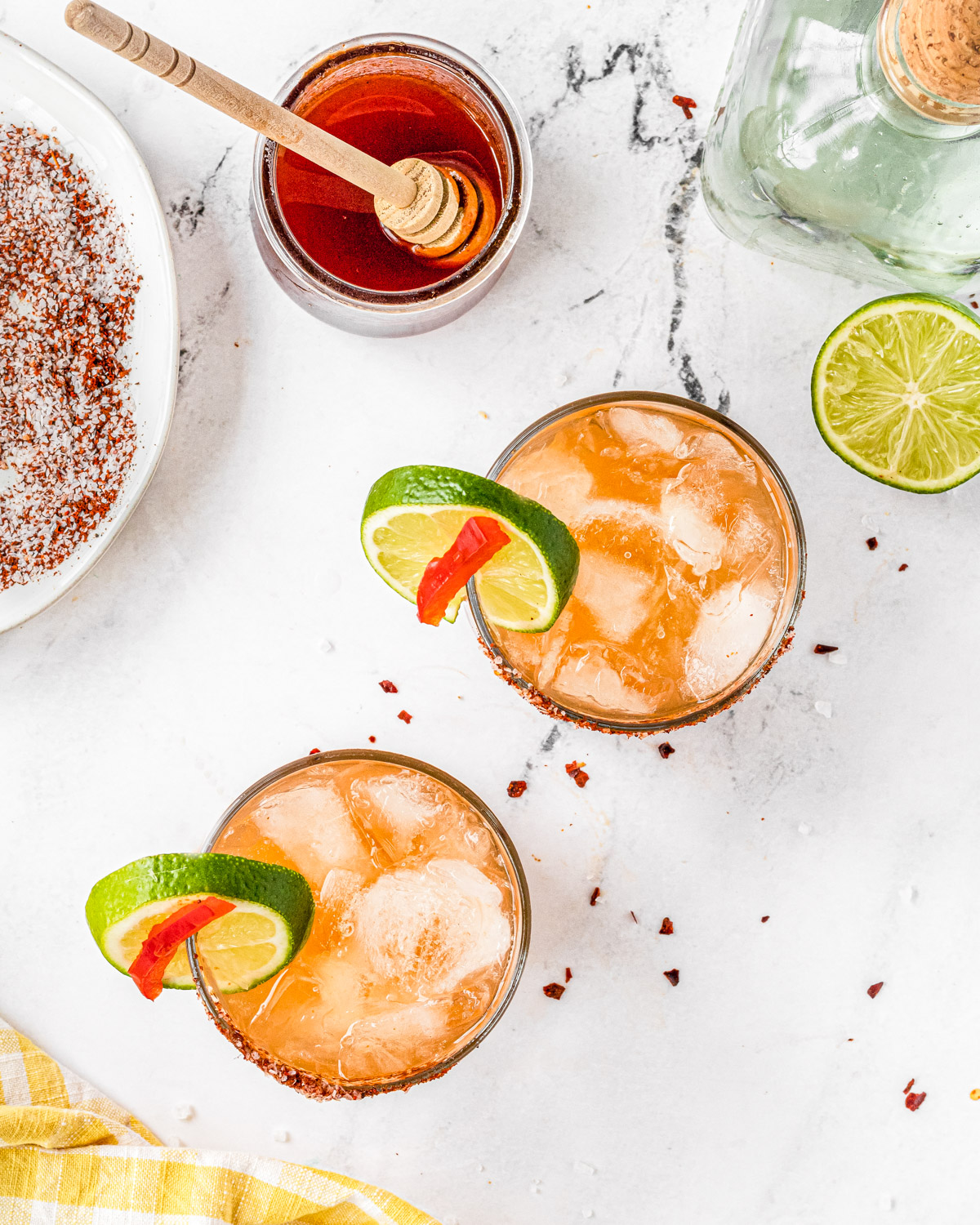 Overhead shot of two margaritas, with hot honey, chili-salt mixture, tequila and lime framing the image.