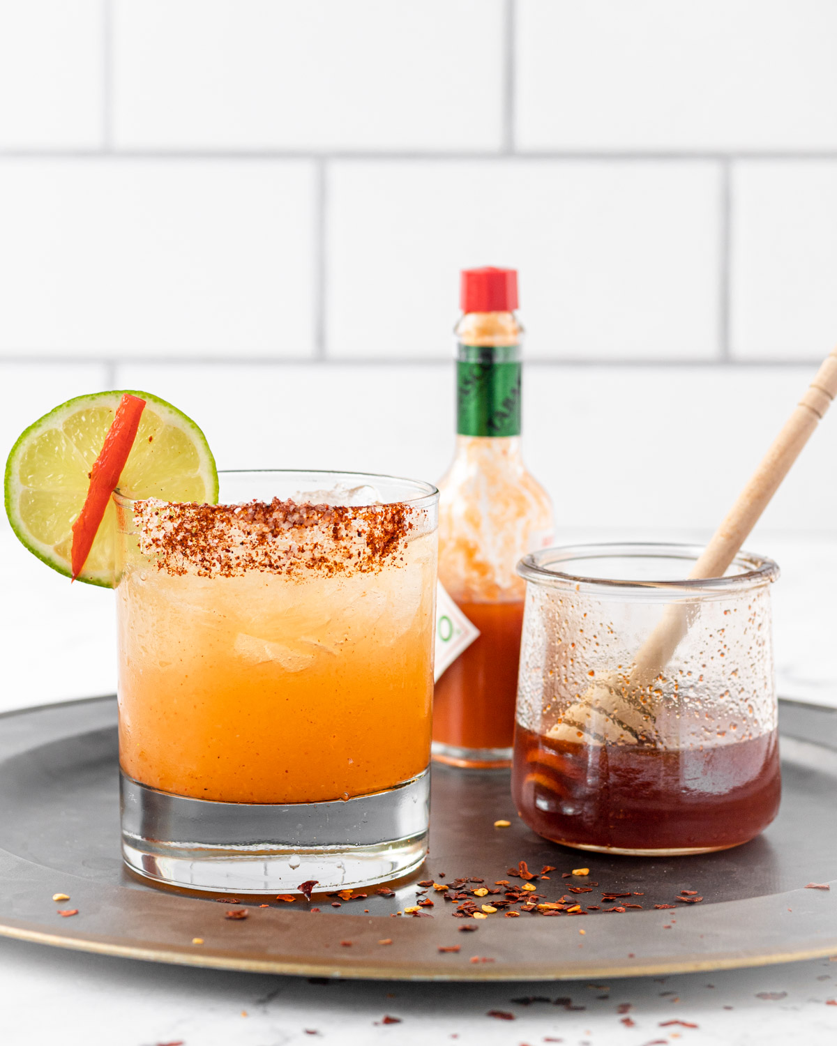 Hot honey margarita on a tray with a bottle of Tabasco and jar of hot honey.