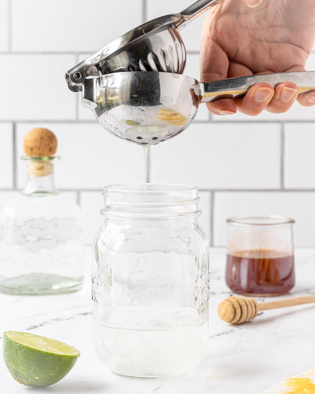Squeezing lime juice into mason jar.