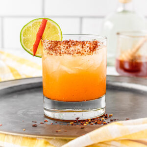 Rocks glass with hot honey margarita, chili-salt rim and a lime and hot pepper wedge.