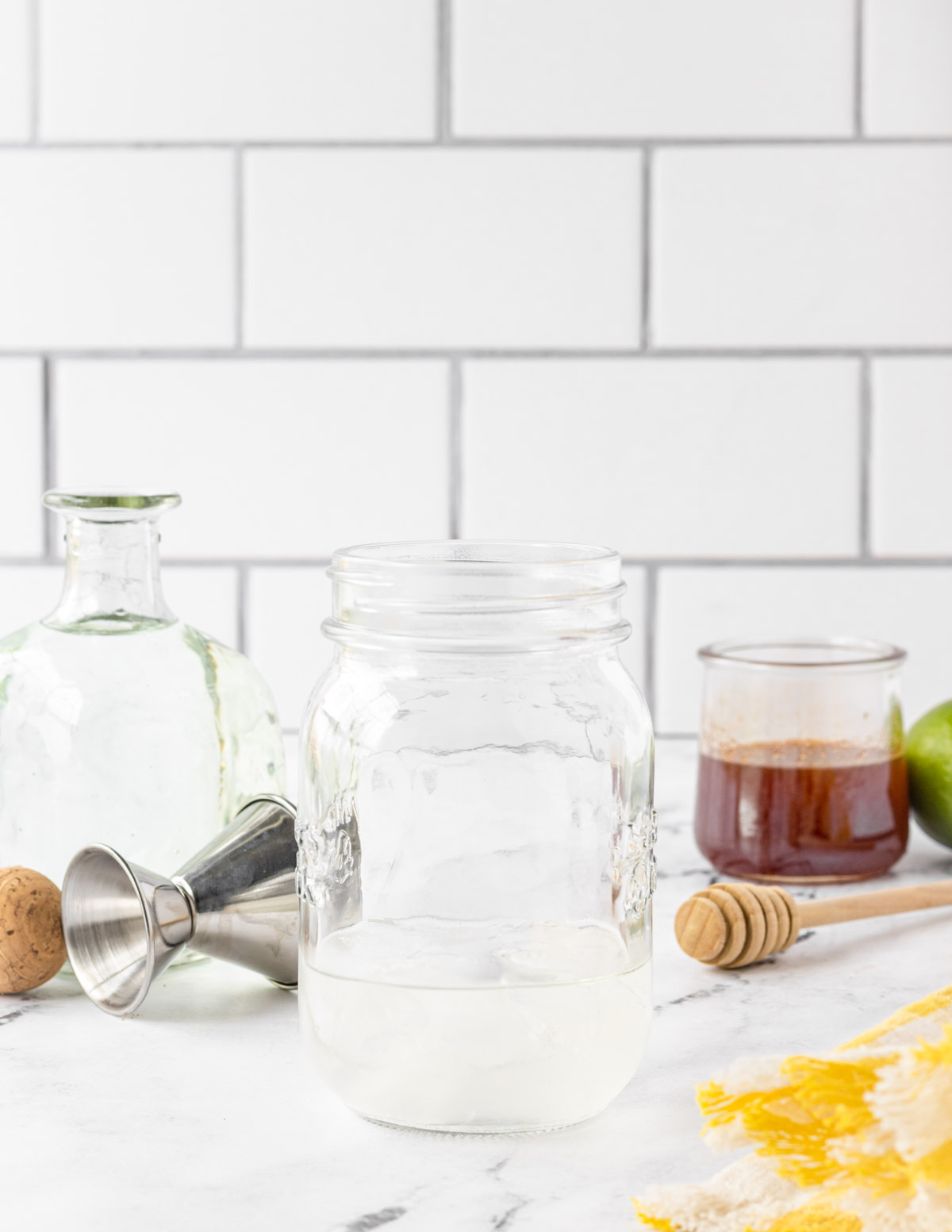 Mason jar with silver tequila added, and hot honey on the side.